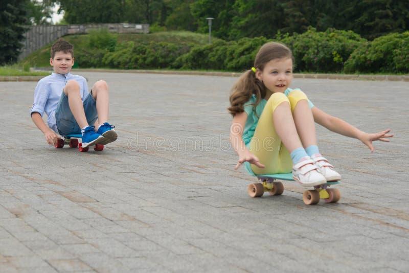 In het Park, in openlucht, een jongen en een meisje die een skateboard berijden, die op het, op de steenblokken zitten royalty-vrije stock fotografie