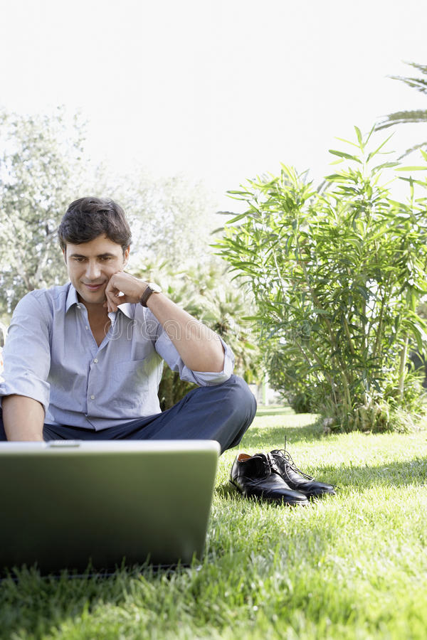 Het Park van zakenmanusing laptop at stock afbeeldingen