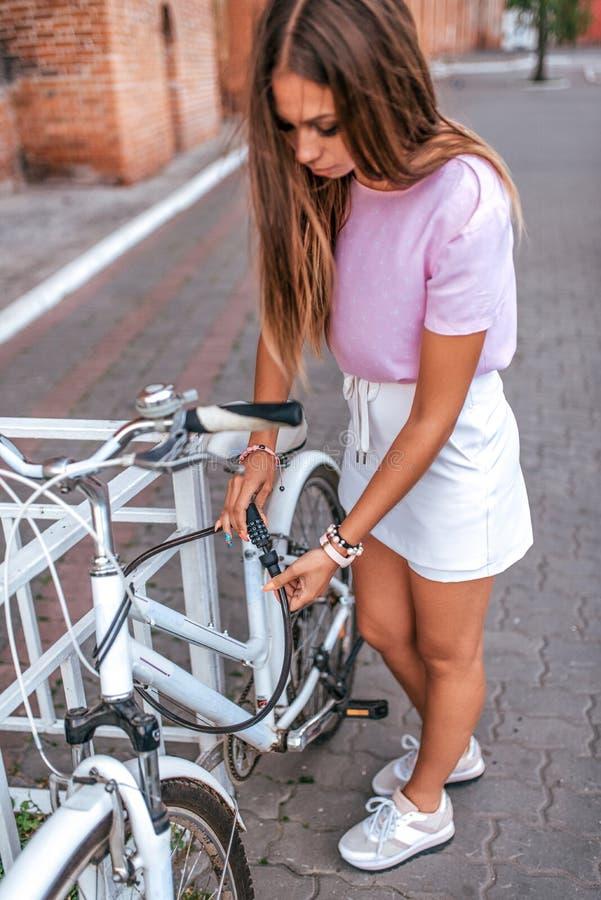 Het parkeren van de de stadsfiets van de meisjeszomer De kabel van het blokkenmetaal zijn fiets Beschermingsbezit van diefstal He stock afbeeldingen