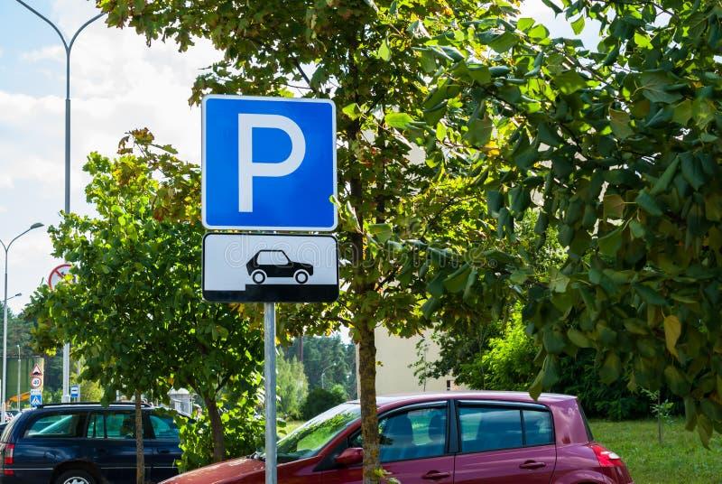 Het parkeren van het verkeerteken voor auto's op een achtergrond die van de stadsstraat tonen hoe te hun voertuigen correct te pl royalty-vrije stock afbeelding