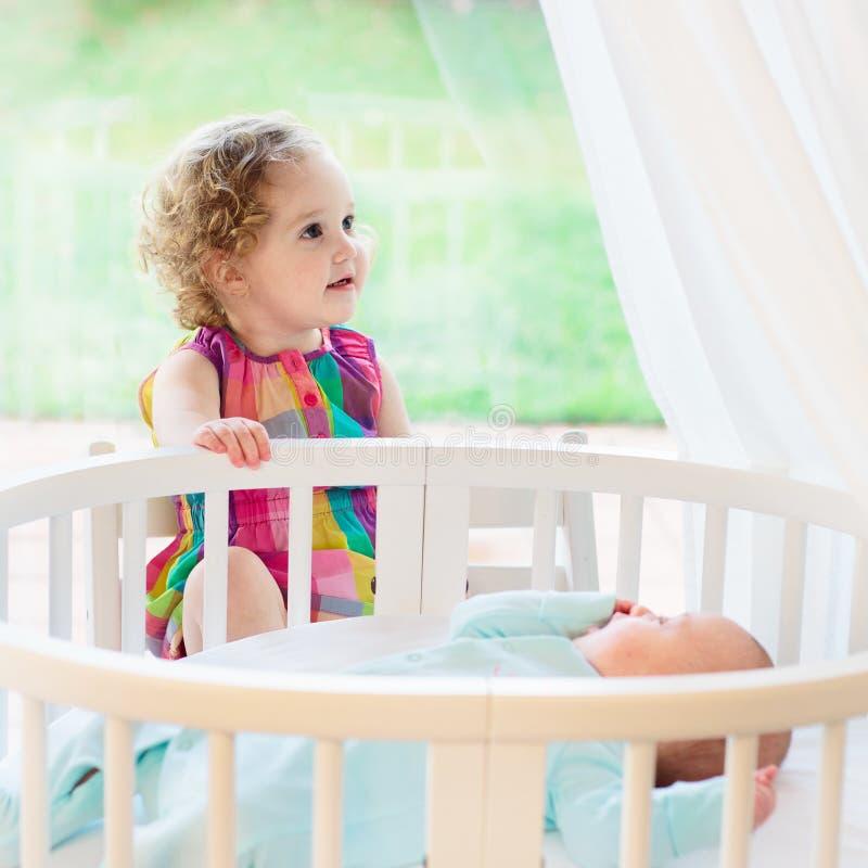Het pasgeboren kind ontmoet zijn zuster stock afbeeldingen