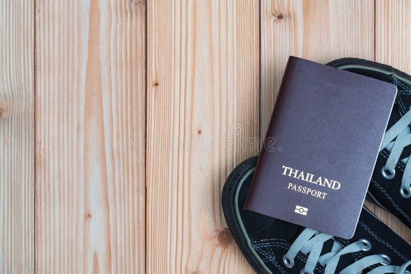 Het Paspoort en de tennisschoenen van de reiziger van Thailand klaar te reizen streven na stock afbeelding