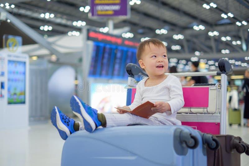 Het paspoort van de het kindholding van de peuterjongen met koffer, zitting op karretje bij luchthaven, wachten voor vertrek stock afbeeldingen