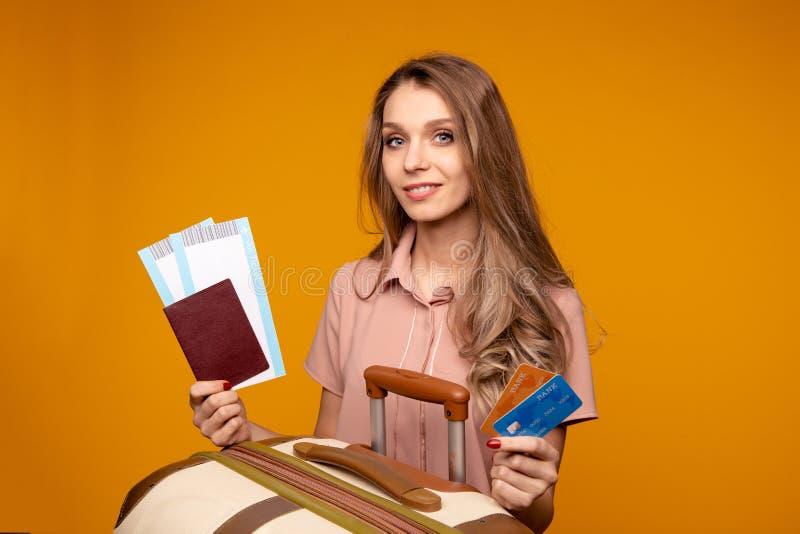 Het paspoort van de de reizigersholding van de Milingsvrouw met kaartje en creditcard Gele muur royalty-vrije stock foto