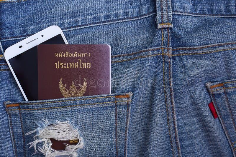 Het Paspoort van Thailand in de zak en smartphone van denimjeans stock foto's