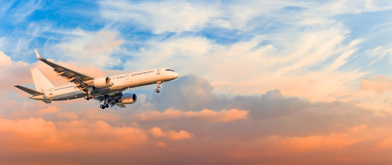 Het passagiersvliegtuig landt benaderingstoestel, tegen de wolken van de zonsonderganghemel, panorama wordt vrijgegeven dat Reisl stock foto's