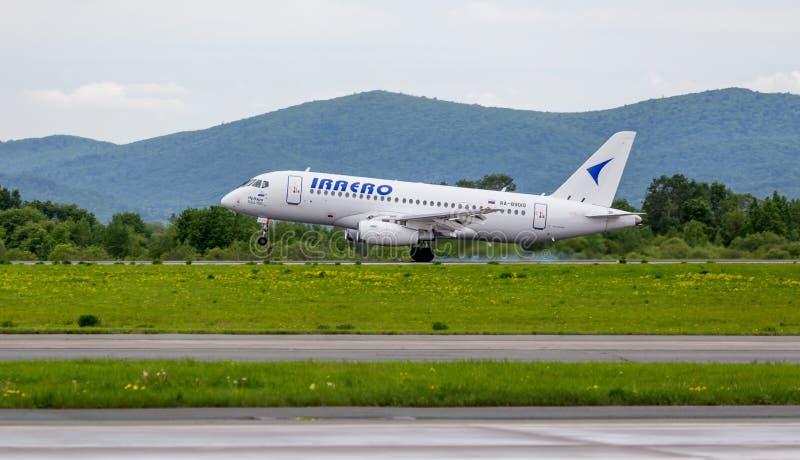 Het passagiersvliegtuig Sukhoi Superjet 100 SSJ 100 van IrAero-bedrijf landt Rook van onder de chassis achter de vliegtuigen stock foto's