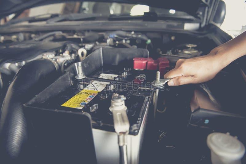 Het passen van een autobatterij met moersleutel stock afbeelding