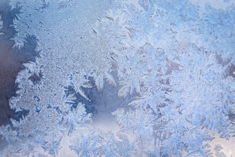 Het patroon van het de winterijs op het bevroren venster stock afbeelding