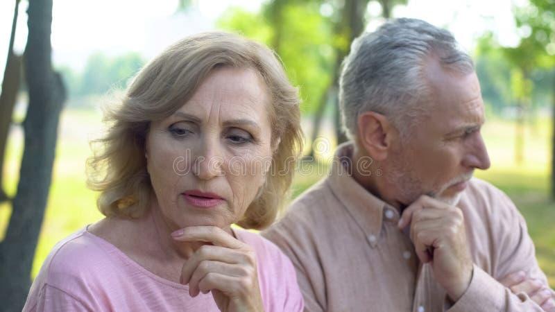 Het peinzende gepensioneerden denken aan probleem, crisis in relaties, verouderde paarscheiding stock foto