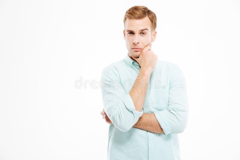 Het peinzende knappe jonge zakenman stading met gevouwen handen en het denken stock afbeelding