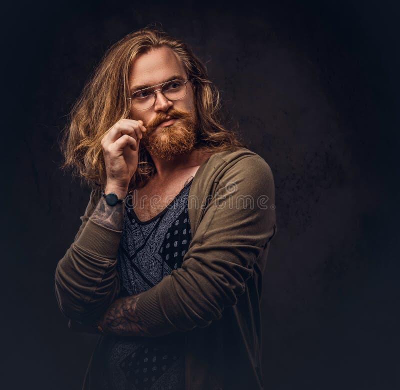 Het peinzende roodharige hipster mannetje met lang luxuriant haar en volledige baard kleedde zich in vrijetijdskleding die met ha stock afbeeldingen