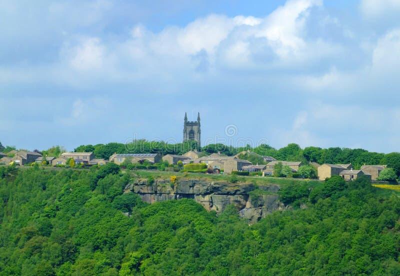Het pennine dorp van heptonstall van over de caldervallei wordt bekeken met historische kerkhuizen en omringend bos dat royalty-vrije stock afbeelding