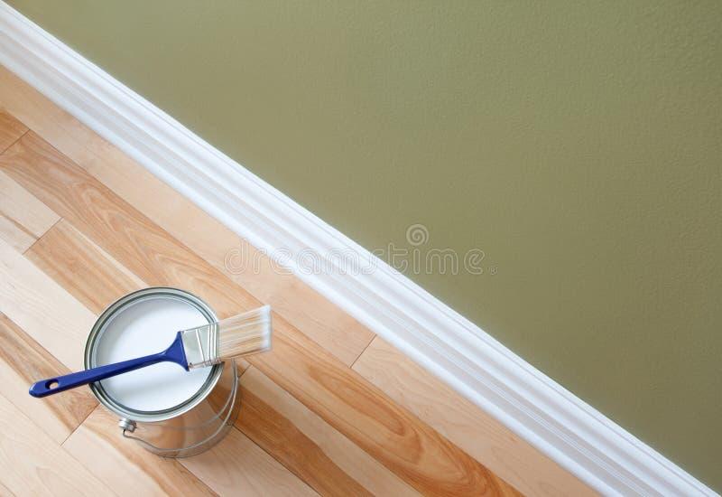 Het penseel en a kunnen van verf op houten vloer stock foto