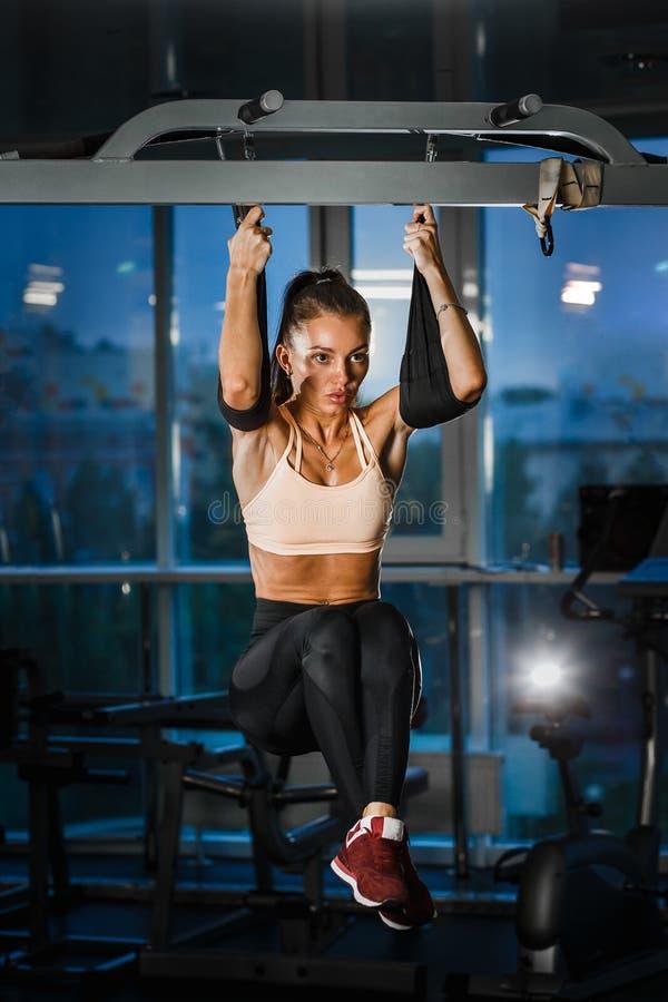 Het perfecte sportmeisje trekt op de rekstok in de gymnastiek uit stock foto's