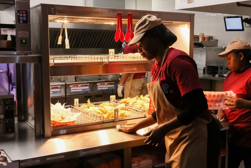 Het personeel in een Popeyes neemt Snel Voedselrestaurant stock foto's