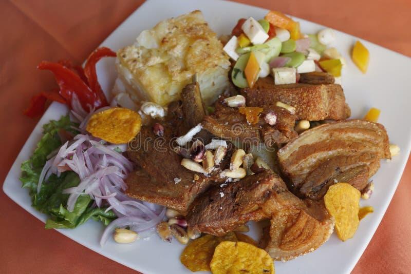 Het Peruviaanse voedsel, Chicharron (gebraden varkensvlees) met aardappels, ui versiert, canchita stock afbeeldingen