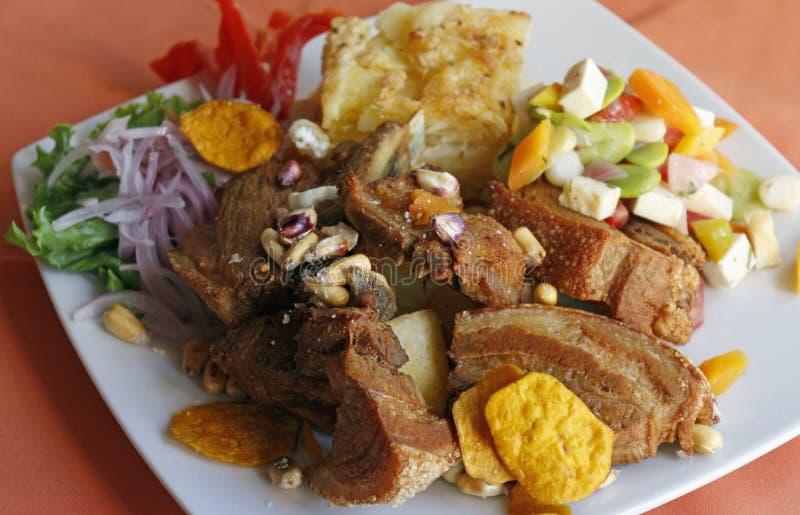 Het Peruviaanse voedsel, Chicharron (gebraden varkensvlees) met aardappels, ui versiert, canchita royalty-vrije stock afbeeldingen