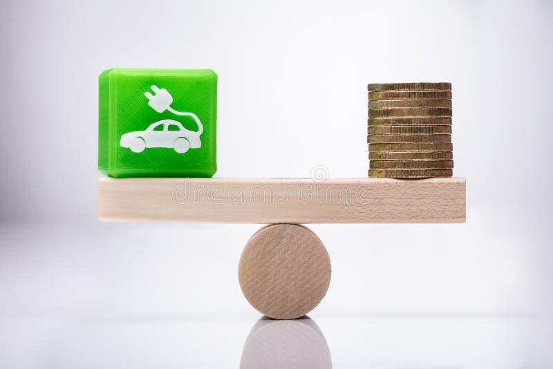 Het Pictogram Kubieke Blok en Muntstukken die van de Ecoauto op Geschommel in evenwicht brengen royalty-vrije stock fotografie