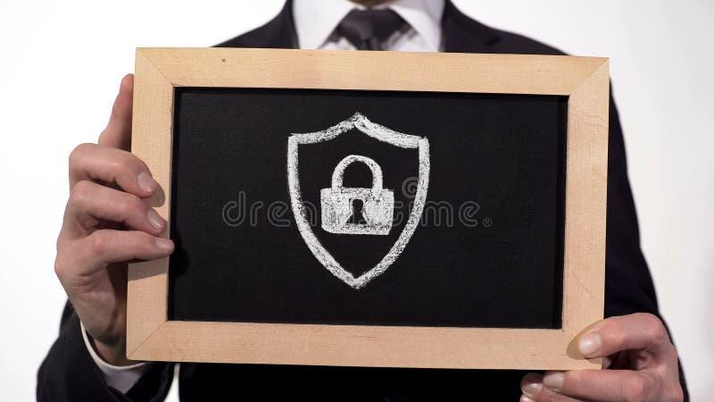 Het pictogram van het veiligheidshangslot op bord in zakenmanhanden wordt getrokken, antivirus veiligheid die stock foto
