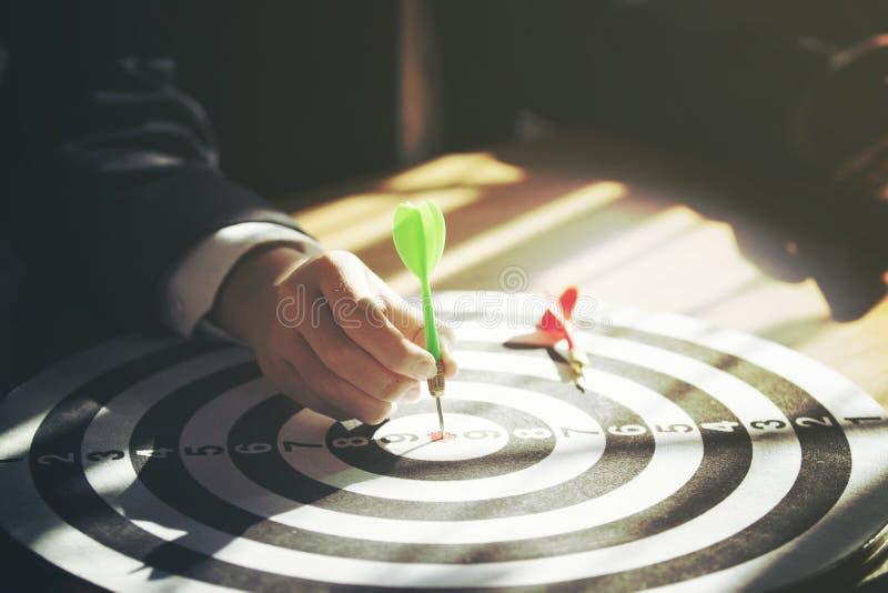 Het pijltje van de zakenmanholding in bijlage aan doel op dartboard royalty-vrije stock afbeeldingen