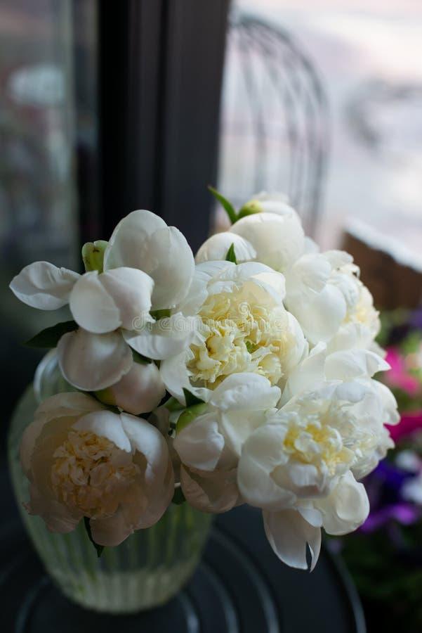 Het pioenenboeket van bloemen op een been binnen het restaurant voor een viering winkelt floristry of huwelijkssalon stock afbeeldingen