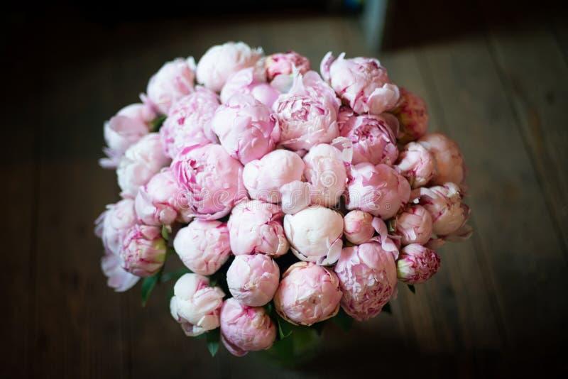 Het pioenenboeket van bloemen op een been binnen het restaurant voor een viering winkelt floristry of huwelijkssalon royalty-vrije stock foto