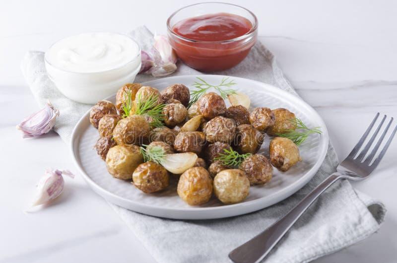 Het plaatsen van een lijst voor heerlijk diner Gebraden knapperige nieuwe aardappels met knoflook en dille, ketchup en smakelijke royalty-vrije stock foto