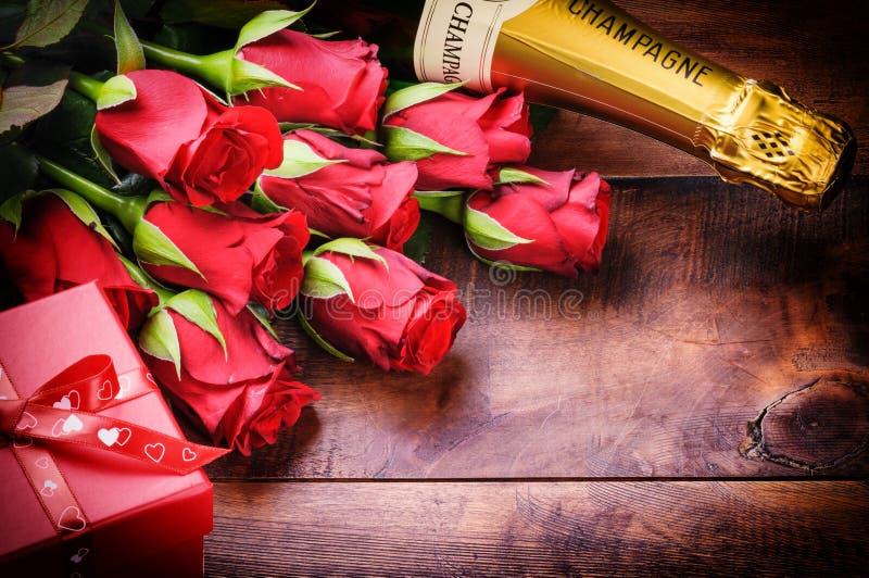 Het plaatsen van Valentine met rode rozen, champagne en gift stock foto