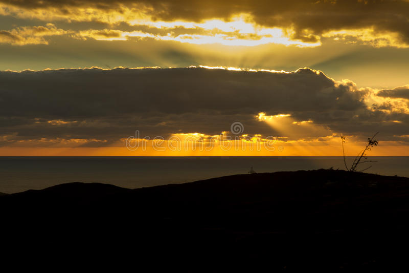 Het plaatsen van zon achter wolk, stralen, overzeese sinaasappel stock fotografie