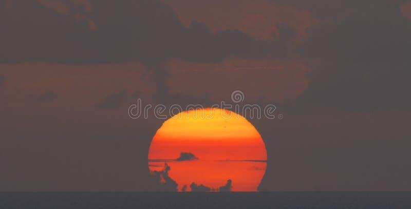 Het plaatsen van zon met wolken stock foto