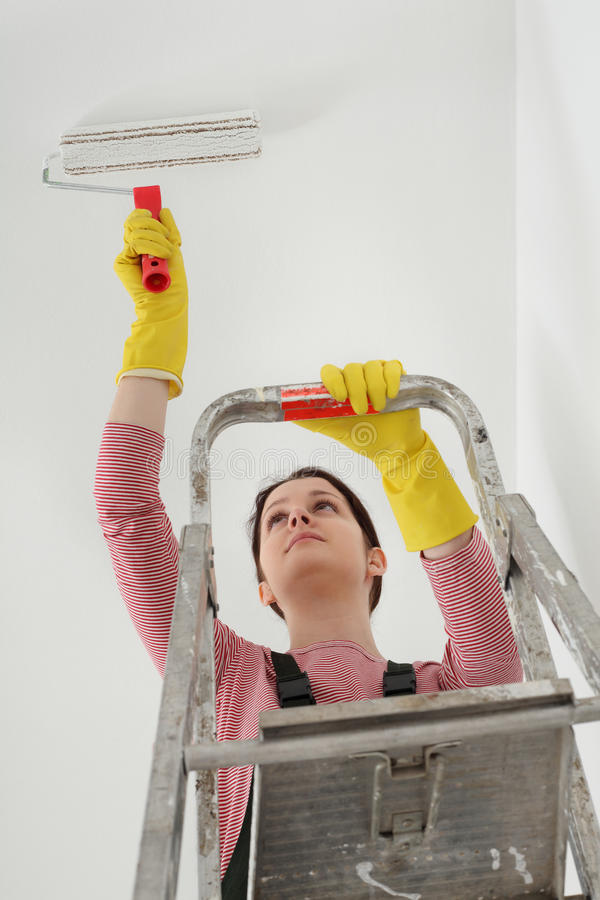 Het plafond van de jonge werknemerverf in een ruimte stock foto