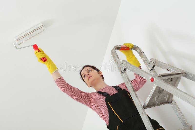 Het plafond van de jonge werknemerverf in een ruimte stock afbeelding