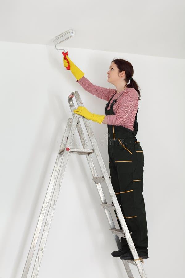 Het plafond van de jonge werknemerverf in een ruimte stock fotografie