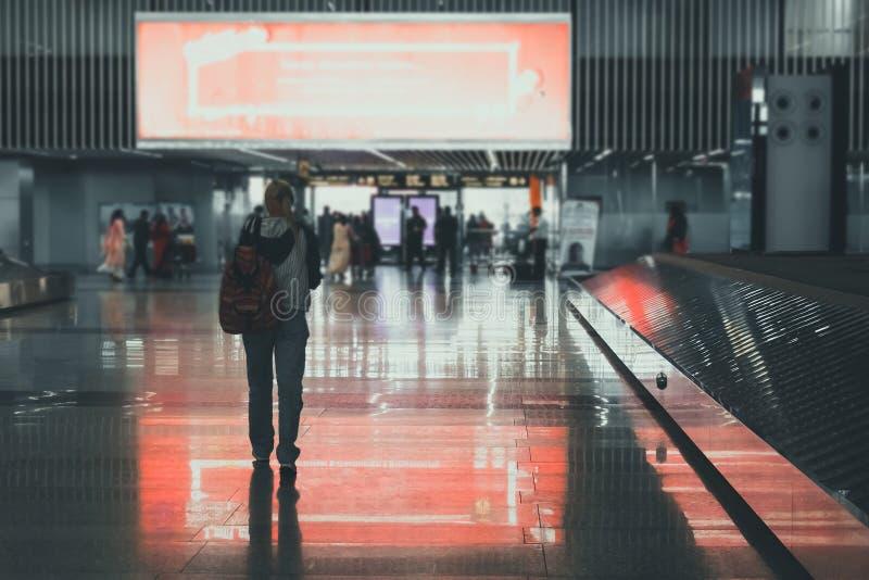 Het plan en de rugzak van de reizigersvrouw zien het vliegtuig bij het venster van het luchthavenglas, de de greepzak van de meis royalty-vrije stock foto