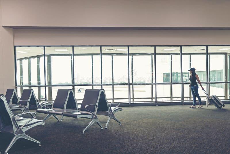 Het plan en de rugzak van de reizigersvrouw zien het vliegtuig bij het venster van het luchthavenglas, de de greepzak van de meis royalty-vrije stock fotografie