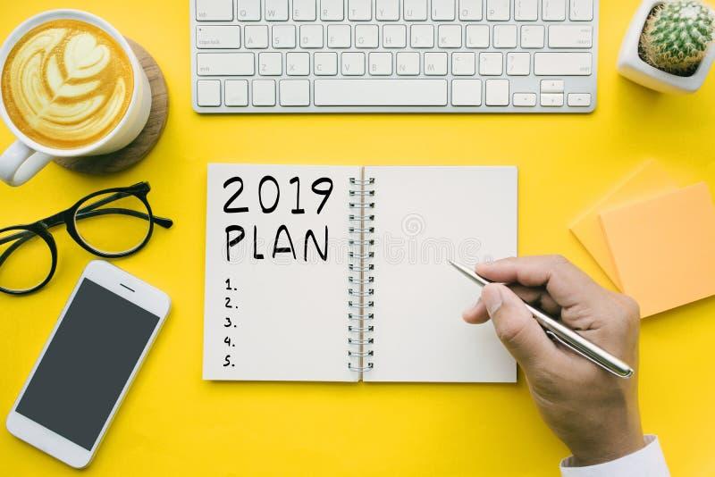 het plan van 2019, controlelijsttekst op blocnote met zakenman en bureau stock foto