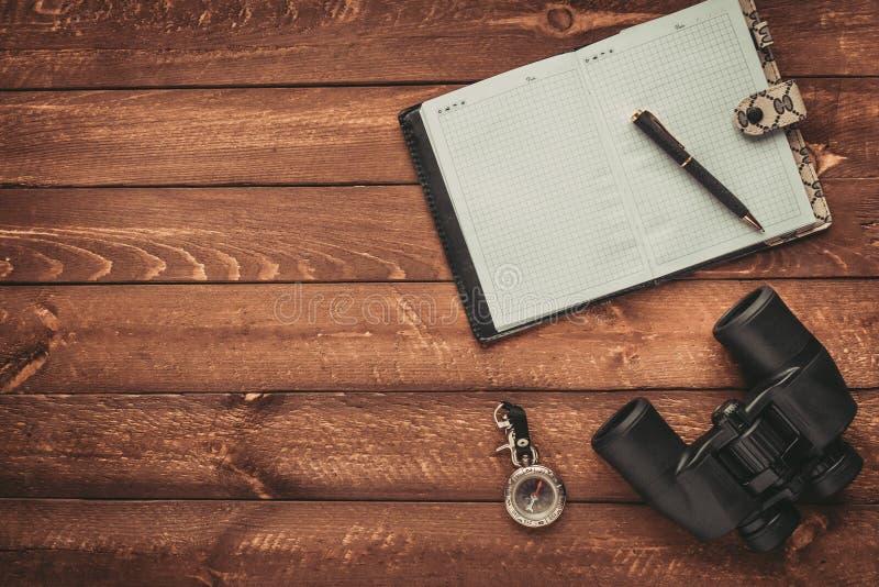 Het plan voor het reizen, verrekijkers, kompas en notitieboekje op bruine houten vloer, vindt en zoekt concept royalty-vrije stock afbeelding