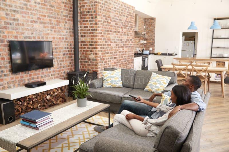 Het Planzitkamer van paarsit on sofa in open het Letten op Televisie royalty-vrije stock fotografie