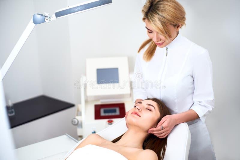 Het plastic Chirurg of van de de Kosmetiekspecialist Gezicht van Examines Woman, Aanrakingen met Handen, het inspecteren Geheelde stock foto