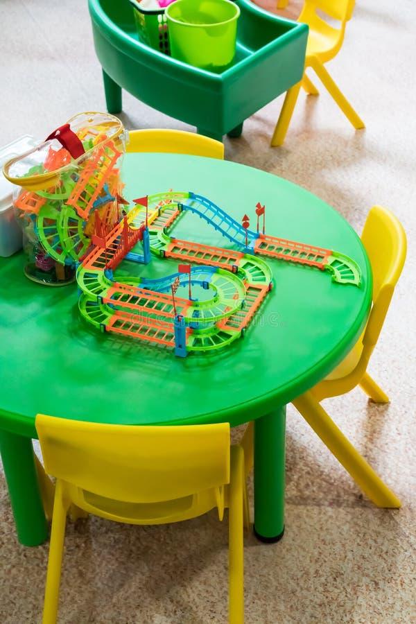 Het plastic stuk speelgoed van de kleurenspoorweg op groene rondetafel royalty-vrije stock afbeelding