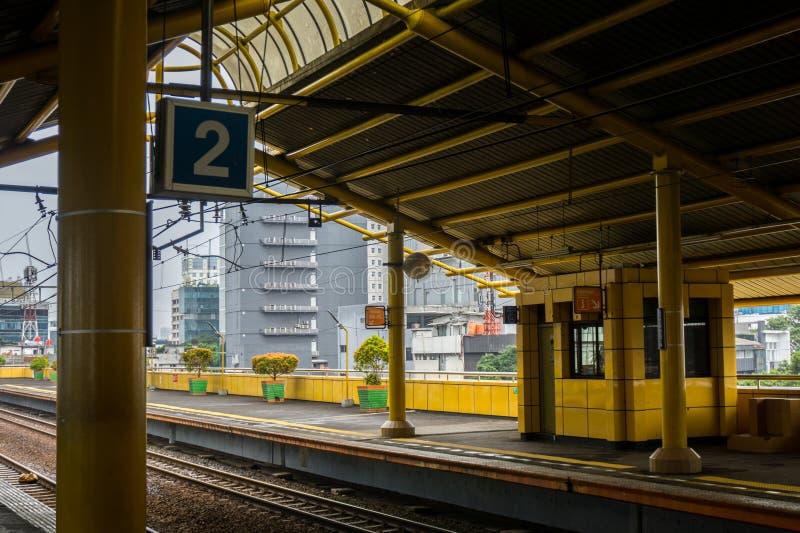 Het platform nummer 2 met blauw die teken scheept aan de gang post met stadskijk op in de foto van Djakarta in Djakarta Indonesië stock fotografie