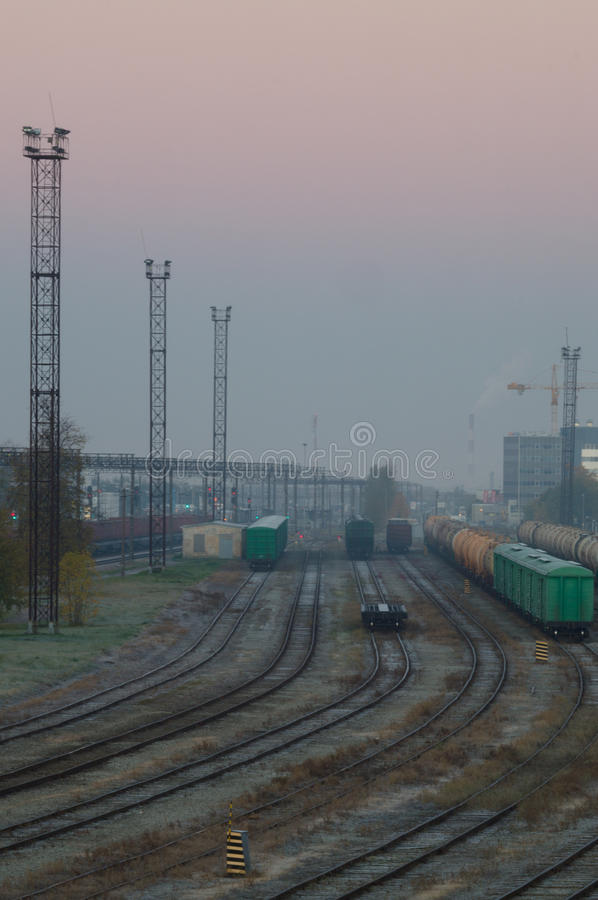 Het platform van de ladingstrein met containers op vroege nevelige ochtend stock afbeeldingen