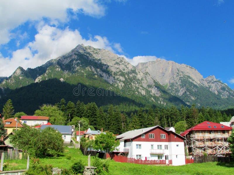 Het platteland huisvest dichtbij rotsachtige berg stock foto