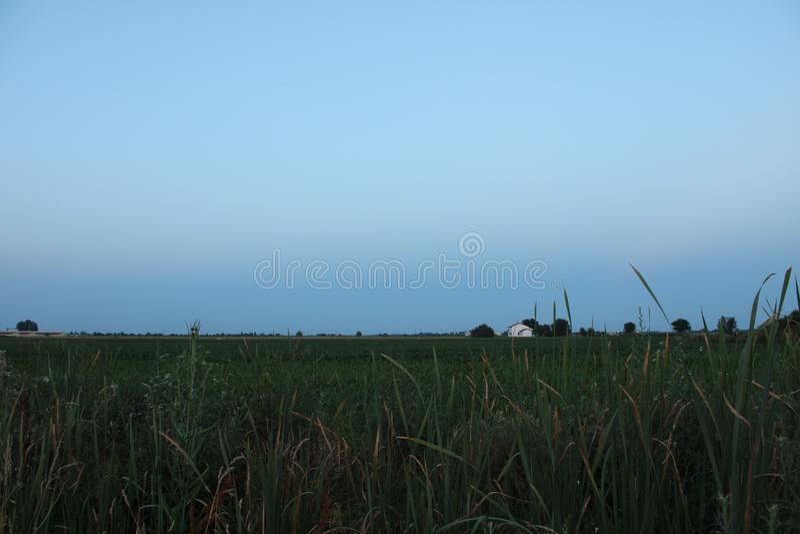Het platteland van Emilia-Romagna na zonsondergang met landbouwbedrijf op de achtergrond royalty-vrije stock afbeeldingen