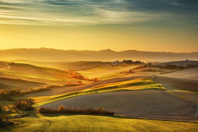 Het plattelands nevelig panorama van Toscanië, rollende heuvels en groen gebied royalty-vrije stock afbeelding