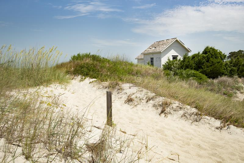 Het plattelandshuisje van het cabineplattelandshuisje op oceaankust in gras en zand op een bochten zonnige dag stock foto