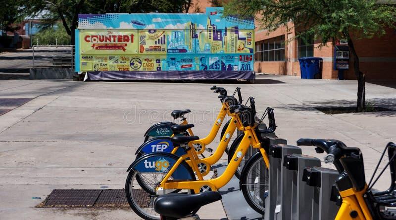 Het plein van de universiteitscampus met fietsenrek, kleurrijke voedselvrachtwagen stock foto's