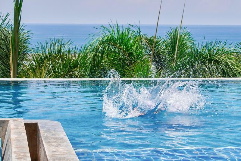 Het plonswater in de pool van a ducked persoon Openluchtpool op achtergrondpalm en overzees Achter mening royalty-vrije stock foto