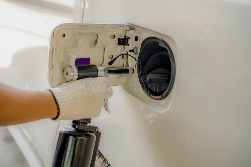 Het pneumatische klinknagelkanon installeert op een lichaamsauto stock fotografie